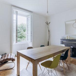 Idées déco pour une salle à manger scandinave fermée avec un mur blanc, un sol en bois clair, une cheminée standard et un manteau de cheminée en bois.