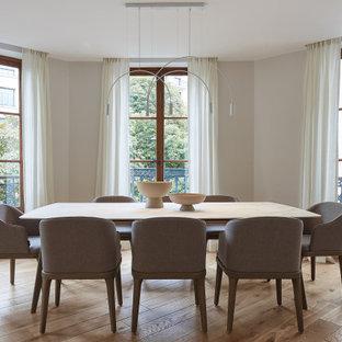 Cette photo montre une salle à manger tendance avec un sol en bois clair, un mur beige et un sol beige.