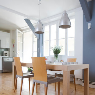 Idées déco pour une salle à manger ouverte sur le salon contemporaine de taille moyenne avec un mur gris et un sol en bois brun.