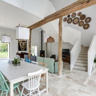 Cette photo montre une grand salle à manger scandinave avec un mur blanc, un poêle à bois, un sol beige et béton au sol.
