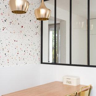 Cette photo montre une salle à manger ouverte sur la cuisine tendance avec un mur blanc.
