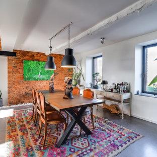 Foto di un'ampia sala da pranzo aperta verso la cucina bohémian con pareti rosse, pavimento in cemento e pavimento grigio