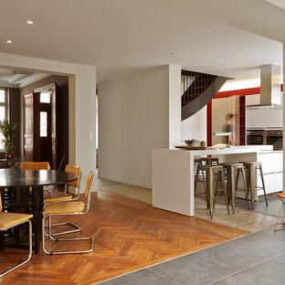 Exemple d'une grande salle à manger ouverte sur le salon éclectique avec un mur blanc et un sol en bois brun.