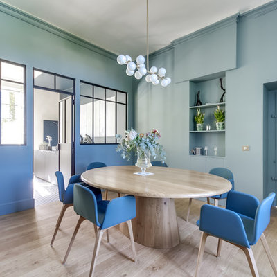 Example of a trendy light wood floor and beige floor enclosed dining room design in Bordeaux with blue walls