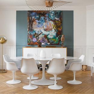 Exemple d'une salle à manger tendance avec un mur blanc, un sol en bois brun, un sol marron et boiseries.