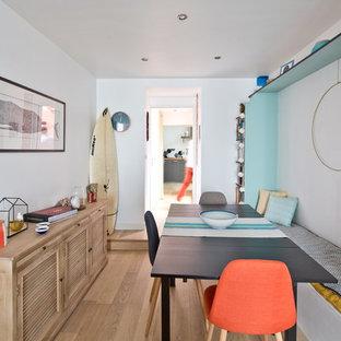 Exemple d'une petit salle à manger bord de mer fermée avec un mur blanc, un sol en bois brun et un sol beige.