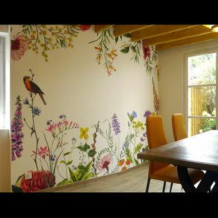 Esempio di una sala da pranzo country con pareti multicolore, parquet chiaro, camino classico, cornice del camino in mattoni, pavimento beige, travi a vista e carta da parati