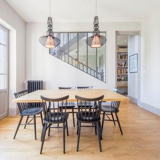 Exemple d'une salle à manger chic de taille moyenne avec un mur blanc, aucune cheminée, un sol en bois brun et un sol marron.