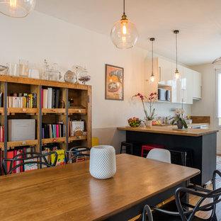 Ejemplo de comedor urbano, de tamaño medio, abierto, sin chimenea, con suelo de madera clara, paredes blancas y suelo multicolor