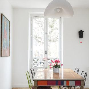 Exemple d'une salle à manger ouverte sur le salon tendance de taille moyenne avec un mur blanc, un sol en bois clair, un sol beige et aucune cheminée.
