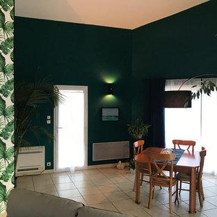 トゥールーズの中くらいのトロピカルスタイルのおしゃれなLDK (緑の壁、セラミックタイルの床、ベージュの床、吊り下げ式暖炉) の写真