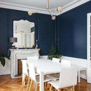 Aménagement d'une salle à manger classique avec un mur bleu, un sol en bois brun, une cheminée standard et un sol marron.
