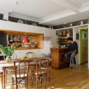 Aménagement d'une salle à manger ouverte sur le salon éclectique de taille moyenne avec un sol en bois brun, un mur blanc et un sol beige.