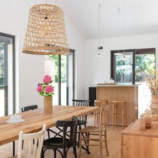 Réalisation d'une grand salle à manger ouverte sur le salon champêtre avec un sol en bois clair.
