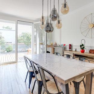 Modelo de comedor urbano, grande, abierto, con paredes blancas, suelo de madera clara, chimenea de esquina, marco de chimenea de piedra y suelo beige