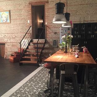 Immagine di un'ampia sala da pranzo aperta verso il soggiorno industriale con pavimento con piastrelle in ceramica e pavimento nero