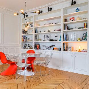 Idées déco pour une salle à manger contemporaine de taille moyenne avec un mur blanc, un sol en bois clair, une cheminée d'angle, un manteau de cheminée en pierre et un sol marron.