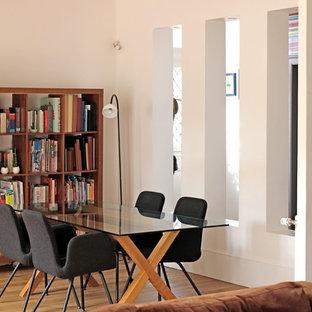Réalisation d'une grand salle à manger ouverte sur le salon design avec un mur beige, un sol en bois brun, une cheminée standard, un manteau de cheminée en pierre et un sol marron.