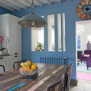 Aménagement d'une salle à manger ouverte sur le salon industrielle de taille moyenne avec un mur bleu, un sol en bois clair et aucune cheminée.