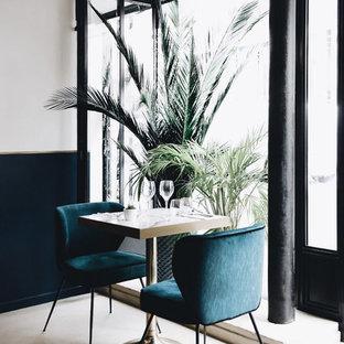Imagen de comedor costero, de tamaño medio, abierto, sin chimenea, con paredes azules, suelo de cemento, marco de chimenea de hormigón y suelo blanco
