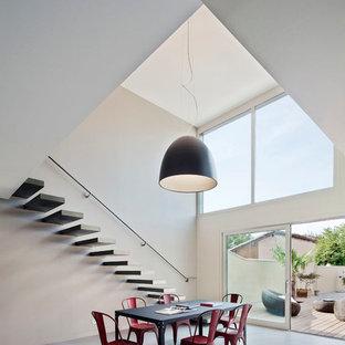 Aménagement d'une très grande salle à manger ouverte sur le salon contemporaine avec un mur gris, béton au sol et aucune cheminée.
