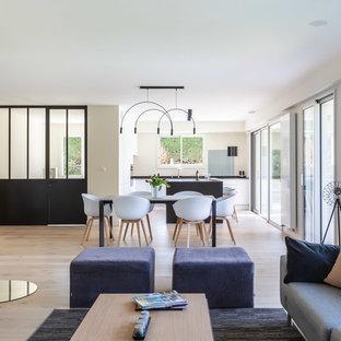 Aménagement d'une salle à manger ouverte sur le salon contemporaine avec un mur blanc, un sol en bois clair, un poêle à bois et un sol beige.