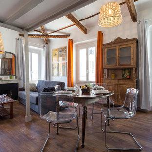 Réalisation d'une salle à manger ouverte sur le salon bohème de taille moyenne avec un mur blanc, un sol en bois foncé, une cheminée standard et un manteau de cheminée en pierre.