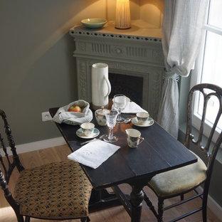 Idee per una piccola sala da pranzo aperta verso il soggiorno classica con pareti verdi, stufa a legna, parquet chiaro e pavimento marrone
