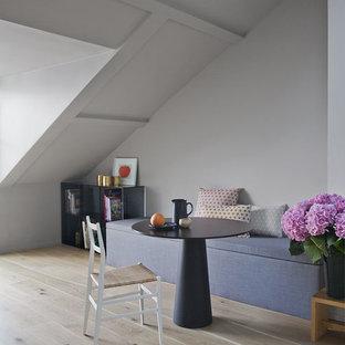 Inspiration pour une salle à manger ouverte sur le salon design avec un mur gris, un sol en bois clair et aucune cheminée.