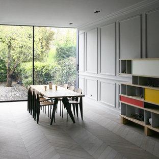Exemple d'une grande salle à manger tendance avec un mur gris, un sol en bois clair et aucune cheminée.