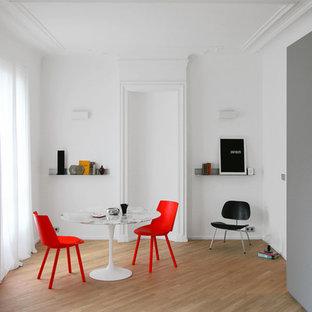 Inspiration pour une salle à manger design avec un mur blanc et un sol en bois clair.