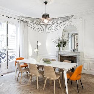 Inspiration pour une salle à manger design de taille moyenne avec un mur blanc, un sol en bois clair, une cheminée standard et un manteau de cheminée en pierre.