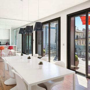 Cette photo montre une très grand salle à manger ouverte sur le salon tendance avec un mur blanc et un sol en bois clair.