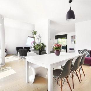 Cette image montre une salle à manger design de taille moyenne avec un mur blanc, un sol en bois clair et aucune cheminée.