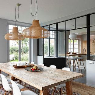 Cette image montre une salle à manger design fermée et de taille moyenne avec un mur gris et un sol en bois clair.
