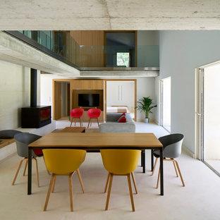 Aménagement d'une grande salle à manger contemporaine avec un mur blanc, béton au sol, un poêle à bois et un manteau de cheminée en métal.