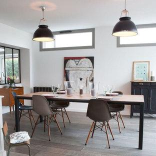 Foto di una grande sala da pranzo aperta verso il soggiorno industriale con parquet chiaro, pavimento marrone, pareti bianche, camino classico e cornice del camino in legno