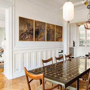 Réalisation d'une petit salle à manger tradition fermée avec un mur blanc et un sol en bois clair.