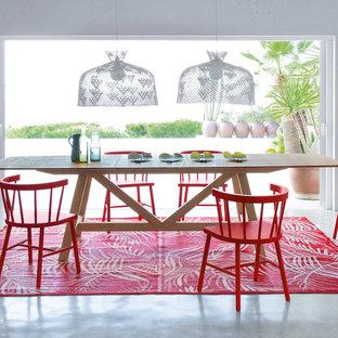Imagen de comedor exótico, grande, abierto, sin chimenea, con paredes blancas y suelo de cemento