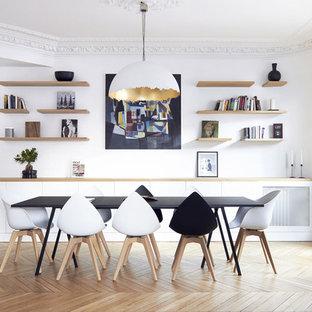 Réalisation d'une salle à manger nordique fermée et de taille moyenne avec un mur blanc, un sol en bois clair et aucune cheminée.