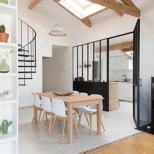 Aménagement d'une salle à manger avec un mur blanc, un poêle à bois, un manteau de cheminée en métal et un sol gris.