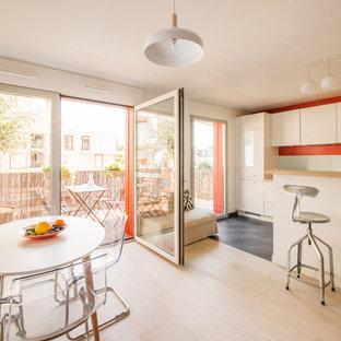 Réalisation d'une salle à manger ouverte sur la cuisine design de taille moyenne avec un mur blanc, un sol en bois clair et aucune cheminée.