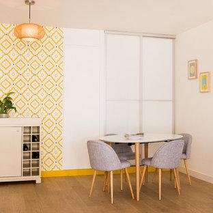 Cette photo montre une grand salle à manger ouverte sur le salon rétro avec un mur jaune, un sol en bois clair et aucune cheminée.