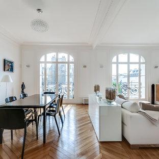 Cette image montre une salle à manger ouverte sur le salon traditionnelle de taille moyenne avec un mur blanc, un sol en bois brun et une cheminée standard.