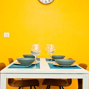 Cette photo montre une salle à manger ouverte sur le salon tendance de taille moyenne avec un mur jaune et un sol en bois brun.