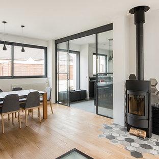 Idée de décoration pour une grande salle à manger design avec un sol en bois clair et un poêle à bois.