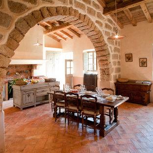 Cette image montre une grande salle à manger ouverte sur la cuisine rustique avec un mur beige et aucune cheminée.