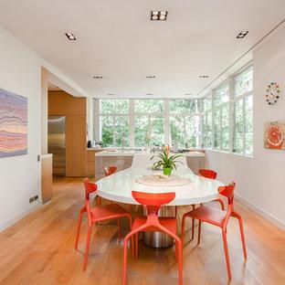 Inspiration pour une grande salle à manger design fermée avec un sol en bois clair et un mur blanc.