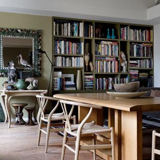 Idées déco pour une salle à manger ouverte sur le salon éclectique de taille moyenne avec un mur vert, un sol en bois clair et aucune cheminée.