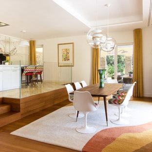 Réalisation d'une salle à manger vintage avec un mur blanc, un sol en bois brun et un sol marron.